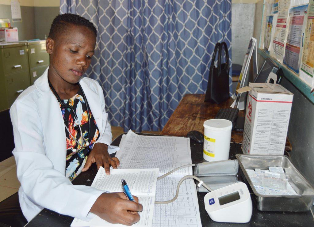 Mourine Andabwa updating patient records at Bukaya Health Center